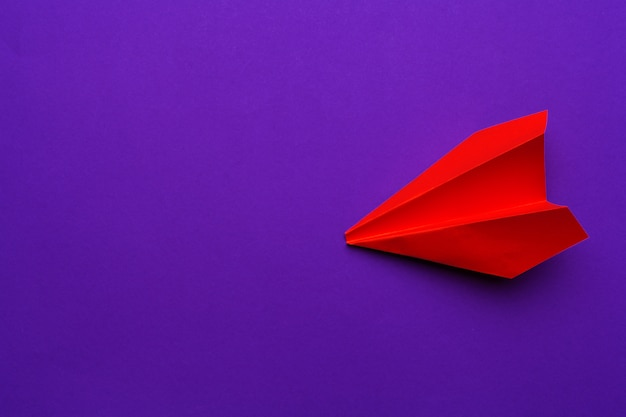 White paper airplane on a purple