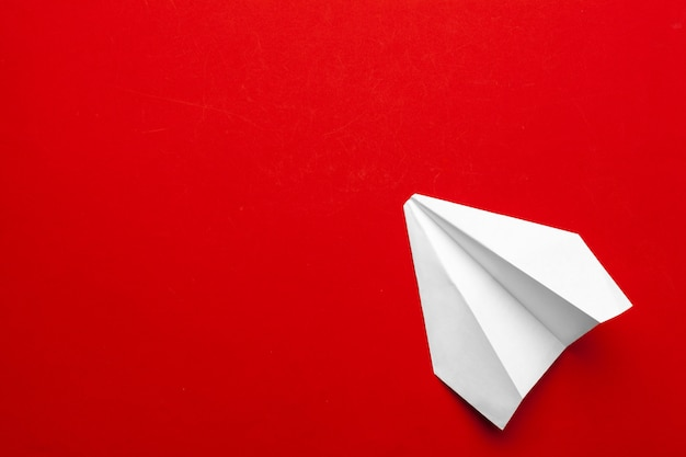 White paper airplane on a red background
