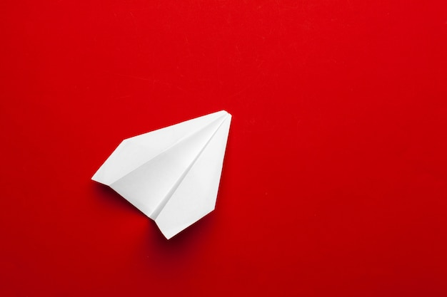 White paper airplane on a red