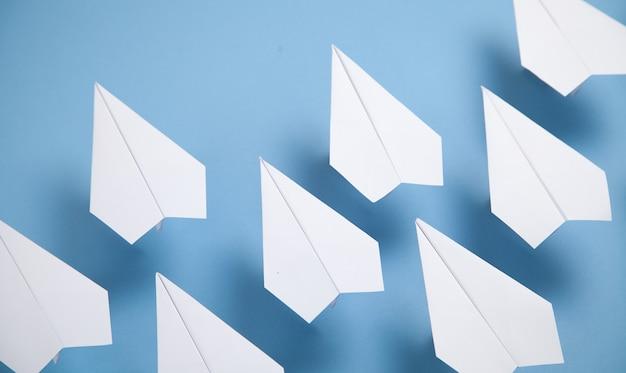 파란색 배경에 흰색 종이 비행기.