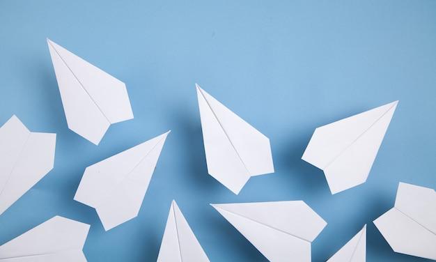 Белые бумажные самолетики на синем фоне.