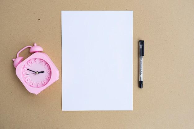 Белая бумага, будильник и ручка на коричневой предпосылке бумаги. минималистский стиль