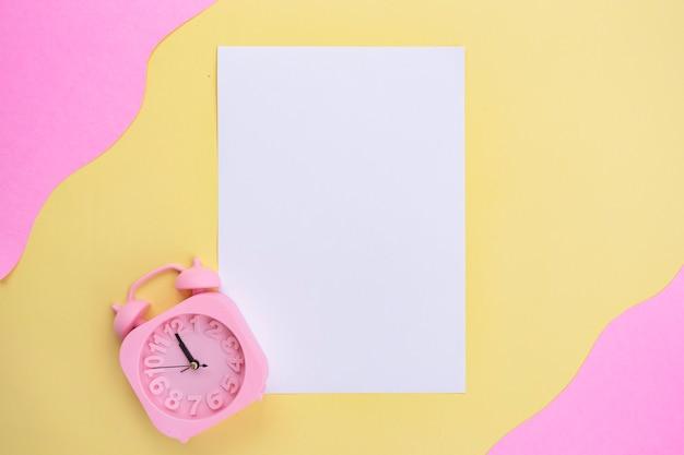 Белая бумага и будильник на желтом и розовом фоне. минималистичный стиль
