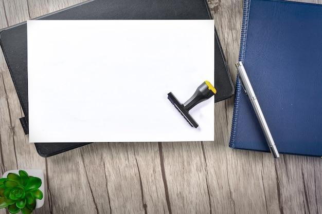 白い紙と木製のテーブルの上のオフィスの文房具。概念的なイメージ