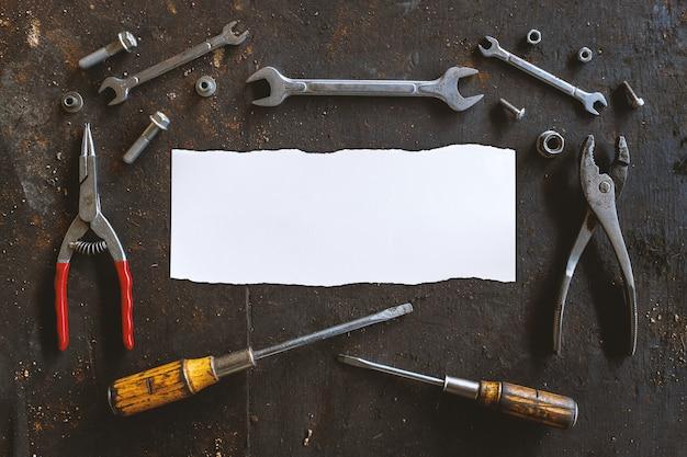 Белая бумага и старые инструменты на фоне черного деревянного пола