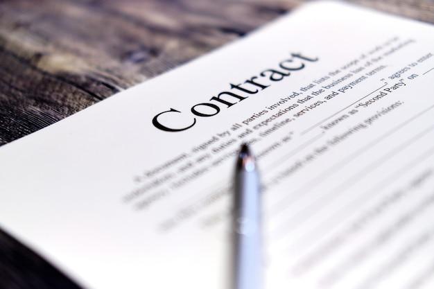 Белая бумага и ручка, шаблон договора на столе