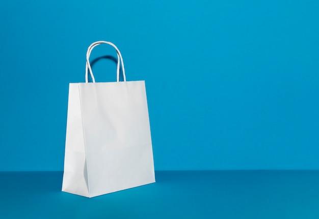 明るい青色のコピースペースの背景に白い紙袋。再利用可能なショッピングバッグ。