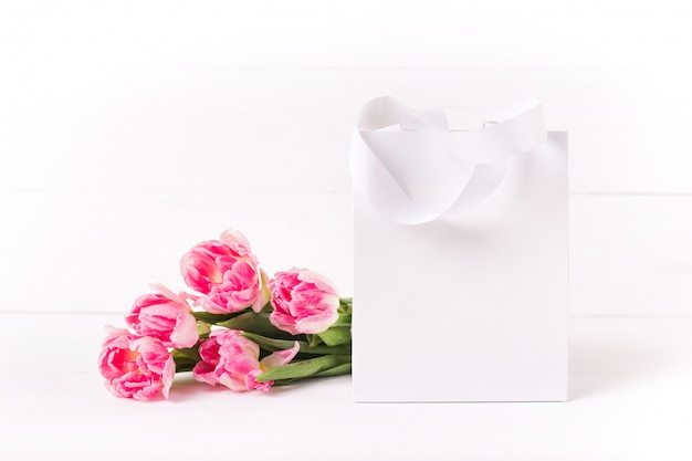 White paper bag on a wooden background. bouquet of beautiful pink tulips. festive mockup.