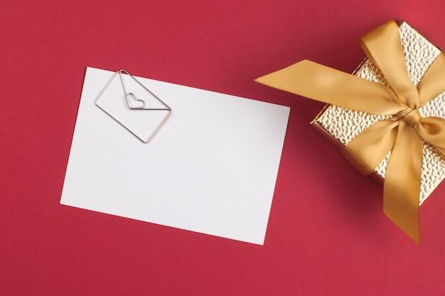 濃い赤の背景に金色のギフトボックスの近くにハート型の封筒の金属ピンとテキストの白い紙の空白のスペース。上面図、フラットレイ。