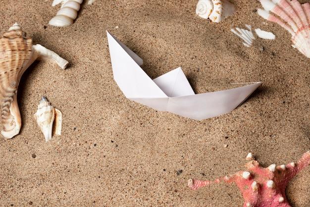 흰 종이 보트는 조개와 불가사리 사이의 바다 모래에 놓여 있습니다