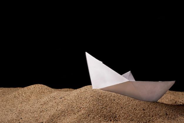 白い紙のボートは、黒い背景の海砂の上にあります