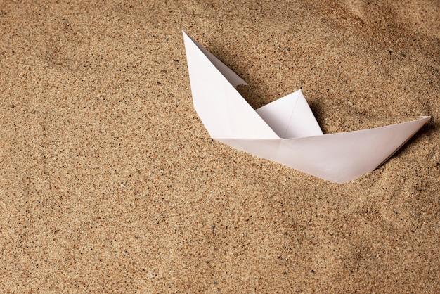 흰 종이 보트는 바다 모래에 놓여 있습니다