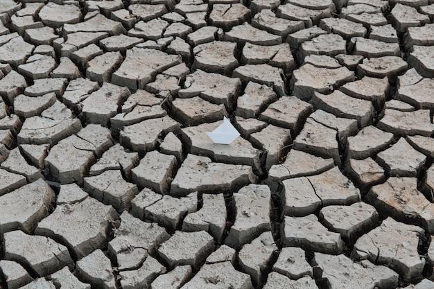 Белый бумажный кораблик на сухой сухой почве с концепцией глобального потепления трещин