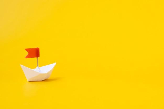 黄色の背景に赤い旗と白い紙のボート。