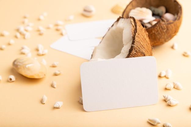 오렌지 파스텔 배경에 코코넛과 조개가 있는 흰색 종이 명함. 복사 공간입니다.
