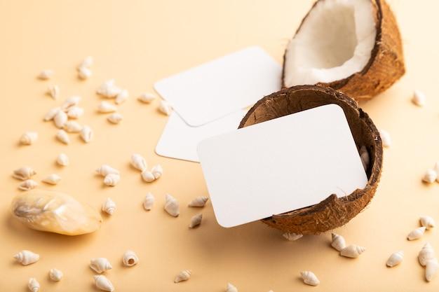 오렌지 파스텔 배경에 코코넛과 조개가 있는 흰색 종이 명함. 측면보기,