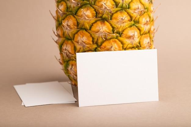 오렌지 파스텔 배경에 잘 익은 파인애플이 있는 흰색 종이 명함. 측면 보기, 복사 공간입니다.