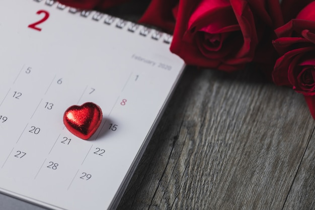 White paper calendar placed on a gray wooden floor, top view and copy space, valentine's day theme