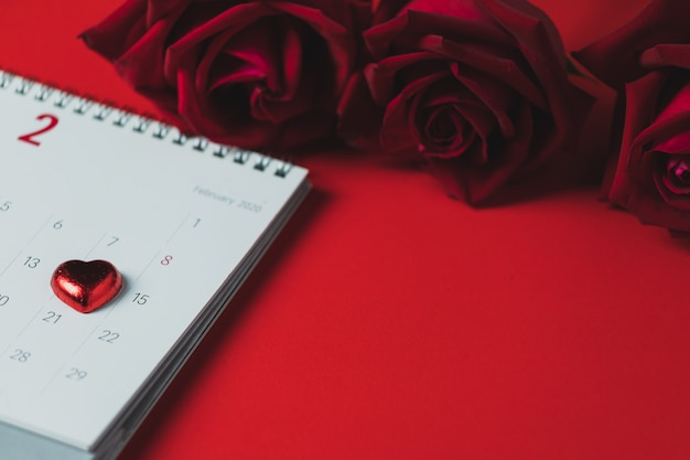 White paper calendar and red rose placed on a red table, top view and copy space, valentine's day theme