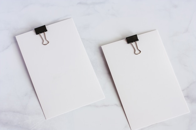 White paper card with binder clip on white marble background