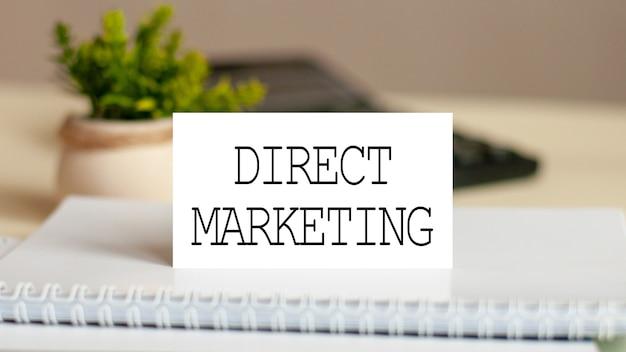 Белая бумажная карточка с текстом прямой маркетинг на калькуляторе. бизнес-концепция.