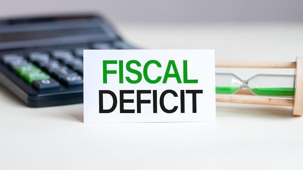 Белая бумажная карточка с текстом фискальный дефицит, калькулятор, песочные часы
