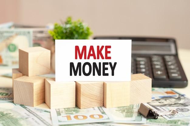 Белая бумажная карточка с текстом зарабатывайте деньги на калькуляторе. бизнес-концепция.