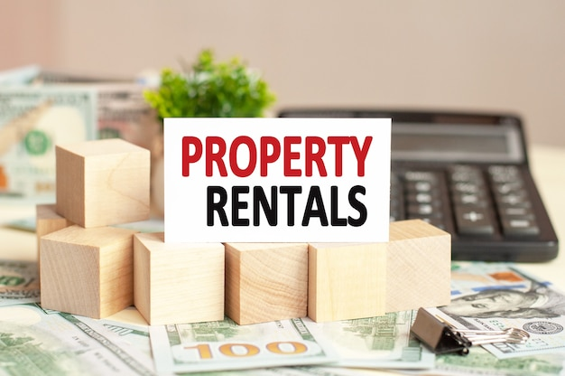 White paper card with text property rentals on the calculator. business concept.
