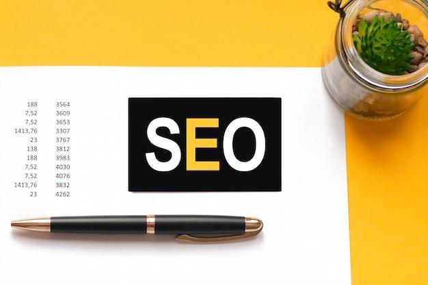 Белая бумажная карточка с текстом seo лист белой бумаги для ручки, цветка на желтой стене. бизнес-концепция. seo - оптимизация поисковых систем