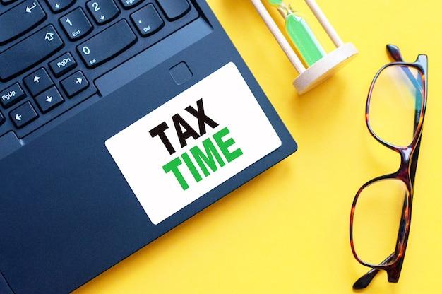 Белая бумажная карточка с текстом налоговое время, лист белой бумаги для заметок, калькулятор, песочные часы, очки в белой стене. бизнес-концепция.