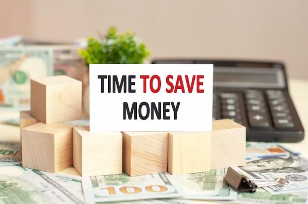 電卓に「お金を節約する時間」というテキストが記載されたホワイトペーパーカード。ビジネスコンセプト。
