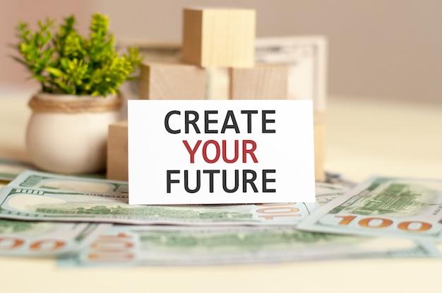 Create your future 텍스트가있는 백서 카드는 종이 돈과 나무 큐브 벽에 있습니다. 비즈니스 개념.