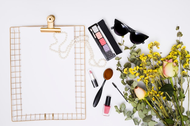White paper on clipboard; necklace; sunglasses; lipstick; nail varnish bottle; makeup brush and flower bouquet on white background