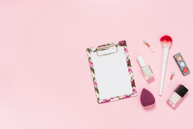 White paper on clipboard with makeup brush; nail polish bottle; eyeshadow palette and blender on pink background