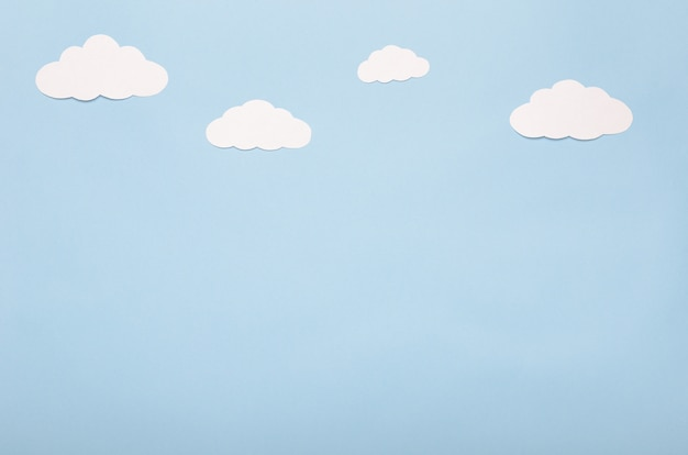 White paper clouds on a blue background