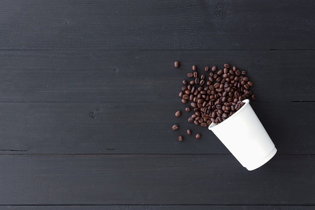 White paper cup and coffee beans on old wooden background. top view