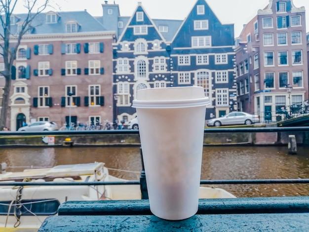 Белый бумажный стаканчик для горячих напитков на фоне архитектуры амстердама. фотография напитков.