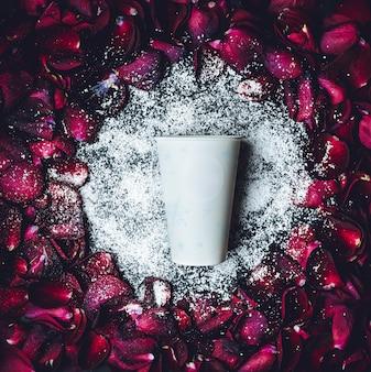 Белая бумажная чашка лежит в белом порошке в кругу красных лепестков роз