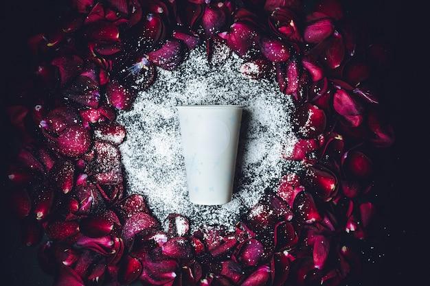 Tazza di carta bianca si trova in polvere bianca nel cerchio di petali di rosa rossa