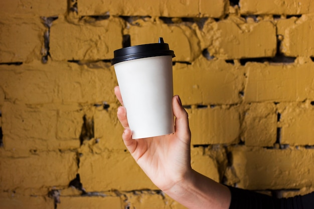 White paper cup with coffee in hand against a yellow brick wall