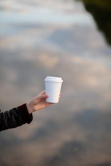 女性の手にコーヒーと白い紙コップ。街でコーヒーを飲む時間。行くコーヒー。瞬間を楽しんで、休憩してください。使い捨ての紙コップのクローズアップ。美味しい温かい飲み物。テキスト、モックアップ用の空白スペース