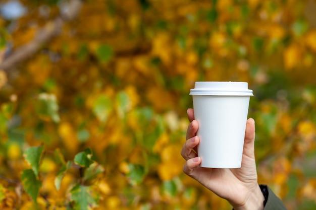 Чашка белой бумаги с кофе в руке женщины. время выпить кофе в городе. кофе с собой. наслаждайся моментом, сделай перерыв. одноразовый бумажный стаканчик крупным планом. вкусный горячий напиток. пустое пространство для текста, макет