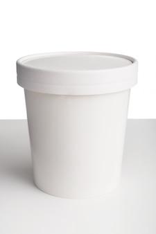 ホワイトスペースに分離された白いテーブルの上のふた付きホワイトペーパーカップ