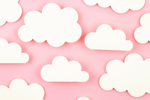 White paper cut out clouds over pink background.