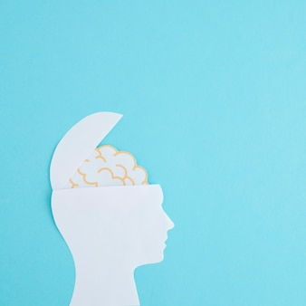 White paper cutout open head with brain on blue backdrop