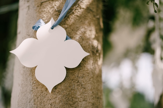 柱の結婚式の装飾のリボンからぶら下がっている白い紙の装飾的な花