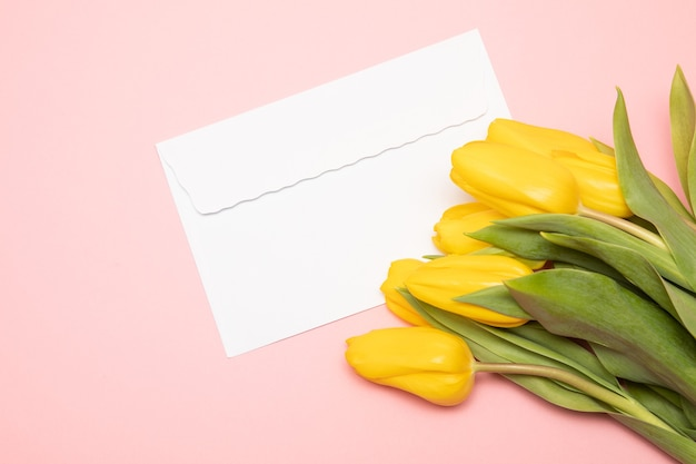 White paper envelope and yellow tulips on a pink background. romantic festive concept, mother's day. mock up