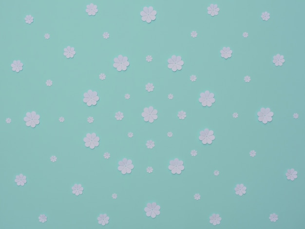 White paper flowers on blue background flat lay style paper art greeting or invitation card