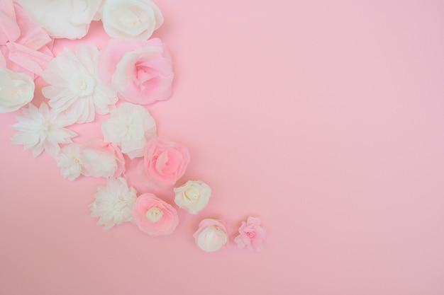 ピンクの背景に白い紙の花。紙から切り取ります。