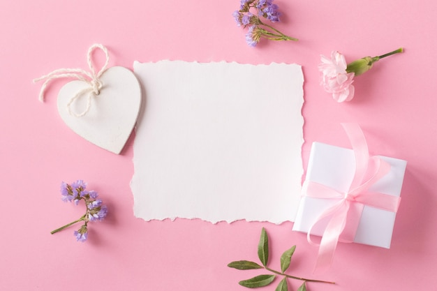 White paper, flowers and wooden heart on pink background. top view, flat lay style.
